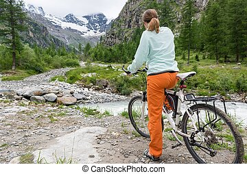 Cyclist stopping before crossing a river
