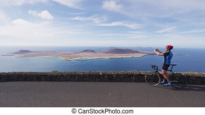 Cyclist tourist taking photo picture with smartphone on biking cycling trip on summer vacation travel. Man riding road bike using phone taking photos on holidays on Lanzarote, Canary Islands, Spain.
