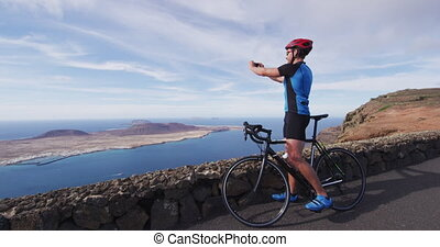 Cyclist tourist taking photo picture with smartphone during biking cycling trip on summer vacation travel. Man riding road bike using phone to take photos during holidays