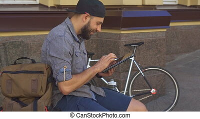 Cyclist uses tablet on the street