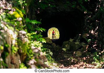 cyclist with mountain bike at the end of a tunnel