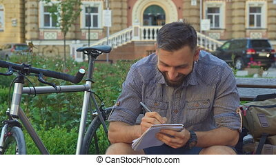 Cyclist writes in his notebook on the bench