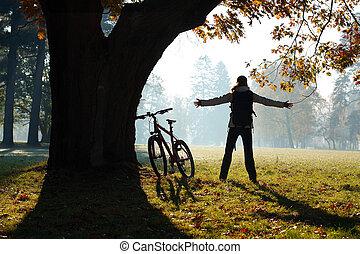 cyklist, stående, kvinna, utsträckt, parkera, omfamna, ...