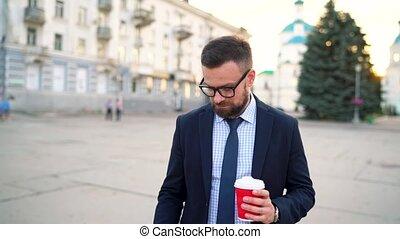 człowiek mówiący, na, smartphone, i, pijąca kawa, pieszy, na dół, przedimek określony przed rzeczownikami, ulica
