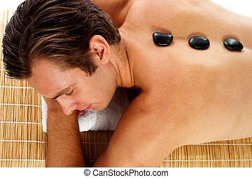 człowiek odprężający, na, masaż, łóżko, z, gorący, kamienie