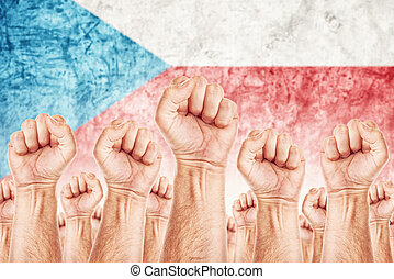 Czech Labour movement, workers union strike concept with male fists raised in the air fighting for their rights, Czech Republic national flag in out of focus background.