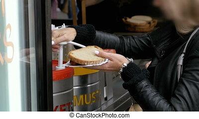 Woman in a Street Cafe Smears Ketchup on a Hot Dog. Prague, Czech Republic