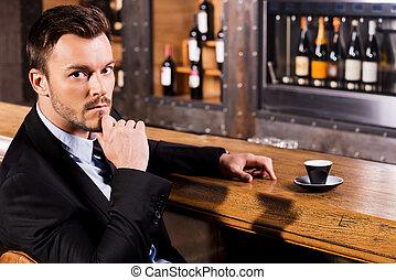 délassant, à, tasse, de, frais, coffee., confiant, jeune homme, dans, formalwear, séance, à, les, compteur barre, et, regarder appareil-photo, à, tasse, de, frais, express, debout, près, lui