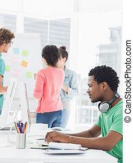 désinvolte, homme, utilisation ordinateur, à, collègues, derrière, dans, bureau