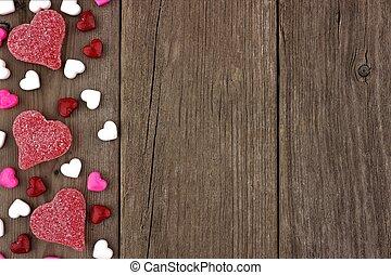 día de valentines, corazón formó, dulce, lado, frontera, en, un, rústico, madera, plano de fondo