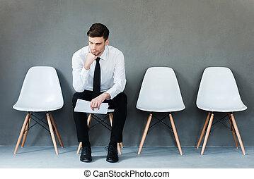 długi, czas, od, waiting., zadumany, młody, biznesmen, dzierżawa papier, i, dzierżawa ręka, na, podbródek, znowu, posiedzenie na krześle, przeciw, szary, tło