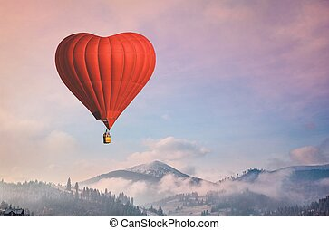 d air balloon in the shape of a heart flying in morning mountains