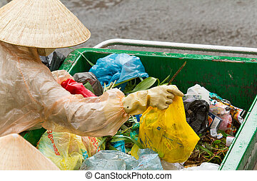 DA LAT, VIETNAM - 28 JULY 2012: Government worker separates the waste on the street for recycling. Pollution is a big problem in Vietnam nowadays. Vietnam, 2012