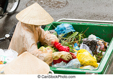 DA LAT, VIETNAM - 28 JULY 2012: Government worker separates the waste on the street for recycling. Pollution is a big problem in Vietnam nowadays. DA LAT, 28 july 2012