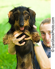 dachshund being held up high