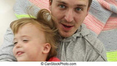 Father and son lying on the floor on a blanket