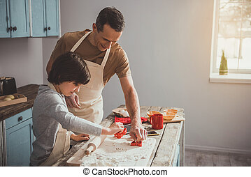 Man and child working with knead in kitchen. They cutting figurines from the dough. Copy space in right side