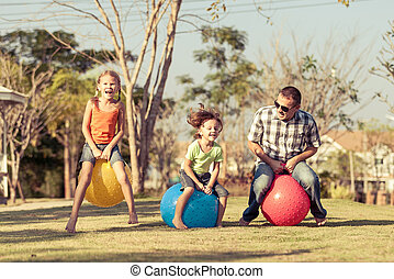 Dad and children playing on the lawn