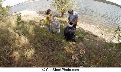 Dad and children scavenge, slow motion - Children cleaning...