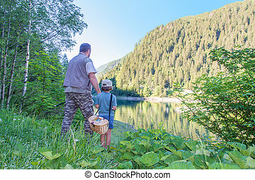 Dad and daughter are going fishing together at a lake in the mountains