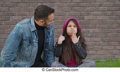 Dad and daughter are sitting, having fun and chewing bubble gum against the backdrop of grass and a brick wall. Concept of mutual understanding, support and happy family