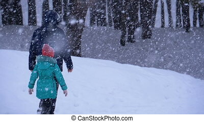 Dad and Daughter are Walking in the Snow in a Pine Forest...