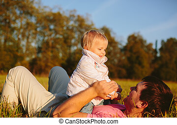 Dad and daughter - Dad plays with her daughter lying on the...
