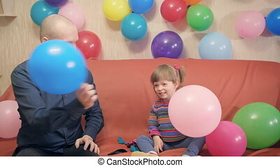 Dad and daughter fight on balloons. They having fun, laughing