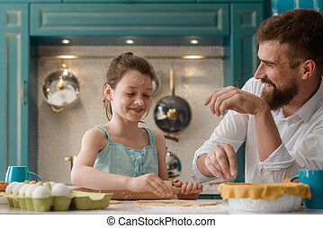 Dad and daughter having fun in the kitchen