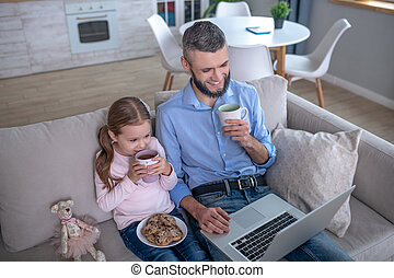 Dad and daughter looking at a laptop drinking tea eating cookies.