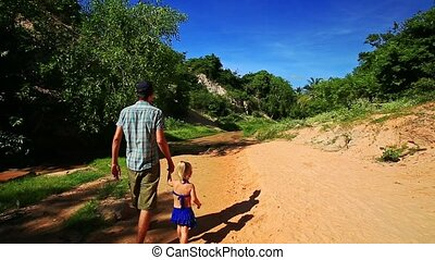Dad and Daughter Walk Hand in Hand on Wet Riverbed -...