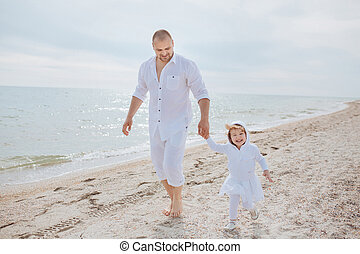 Dad and daughter walking along the beach