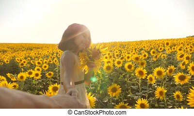 Dad and daughter walking along the field with sunflowers at...