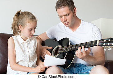 Dad and his daughter compose a song on the guitar.