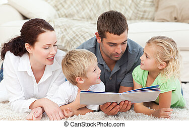 Dad and his family reading a book together lying on the ...