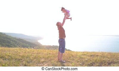 Dad and his little daughter are enjoying the sunset on the shore of a mountain lake.