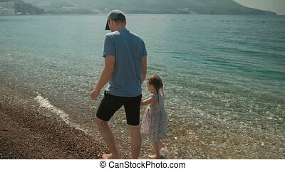 Dad and his little daughter are walking along the beach of the sea.