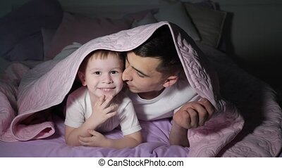 Dad and his little son is playing hiding under the blanket...