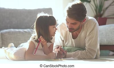 Dad and kid daughter draw with pencils on warm floor