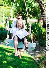 Dad and kid having fun swinging together