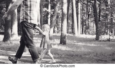 Dad and little baby girl walking in a park