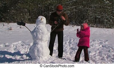 Dad and little daughter make a snowman in the meadow near the forest.
