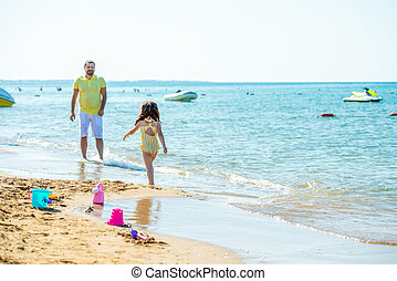 Dad and little girl play, run on the beach and fool around on the sea coast. Family vacation at sea with a child.