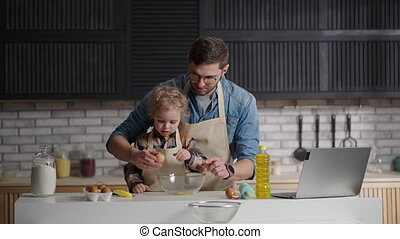 dad and little son are spending time together at kitchen, child is studying to cook, breaking eggs in bowl