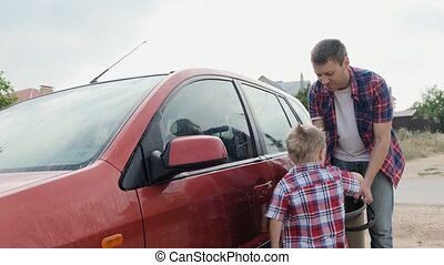 Dad and little son in checkered shirts wash the red car slow motion