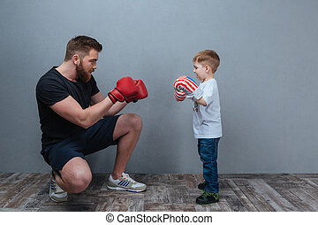 Dad and little son playing in boxing gloves together
