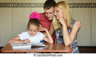 Dad and Mom lovingly watching my daughter first-grader who...