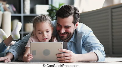 Dad and small daughter using digital tablet lying on floor
