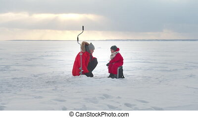 Father teaches son the basics of winter fishing