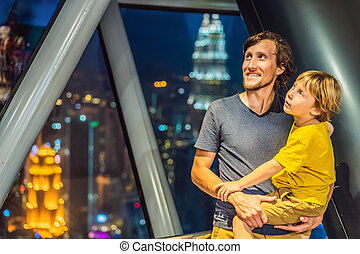 Dad and son are looking at Kuala lumpur cityscape. Panoramic view of Kuala Lumpur city skyline evening at sunset skyscrapers building in Malaysia. Traveling with kids concept